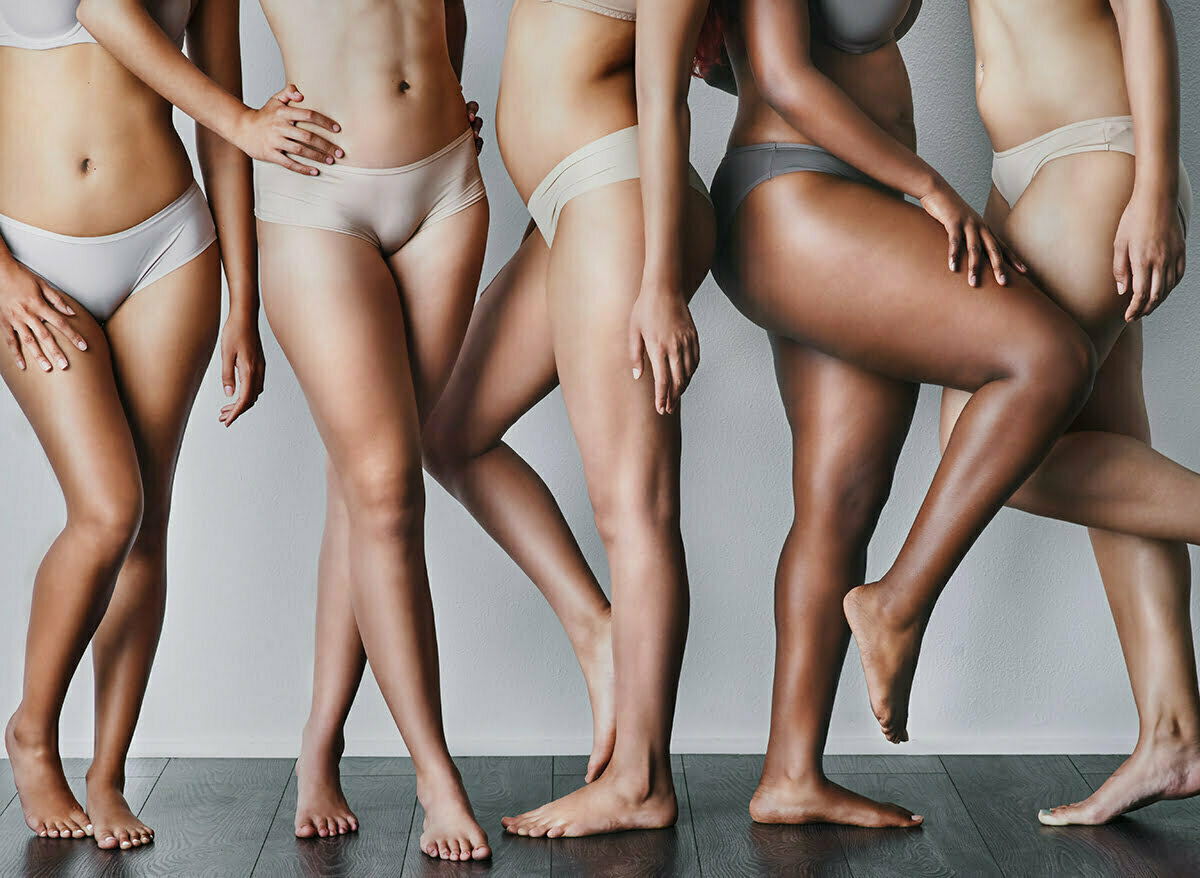 Five women wearing grey underwear are pictured from the abdomen down with smooth legs pose together
